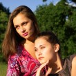 Two girls leaning in sunset light outdoors — Stock Photo