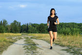 Woman jogging outdoors in summer — Stock Photo