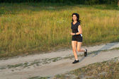 Woman jogging outdoors in forest road — Stock Photo