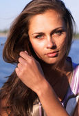 Beautiful girl with long hair at the river shore — Stock Photo