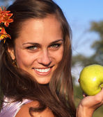 Woman with apple with flower in hair — Stok fotoğraf