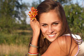 Smiling woman with flower in hair — Stockfoto