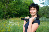 Woman with dumbbells outdoors — Stock Photo