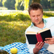 Young man reads book — Stock Photo