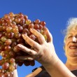 Stock Photo: Mature woman and grapes