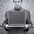 Businessman and laptop with empty screen — Stock Photo
