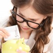 Little girl with piggy bank and money — Stock Photo #3249194