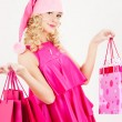 Cheerful santa helper girl with shopping bags — Stock Photo