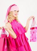 Cheerful santa helper girl with shopping bags — Stock Photo