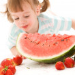 Little girl with strawberry and watermelon - Stockfoto