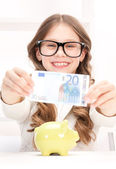 Petite fille avec piggy bank et de l'argent — Photo