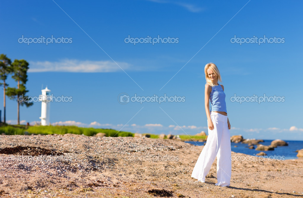 Happy woman in striped vest on the seashore — Stock Photo #3262507