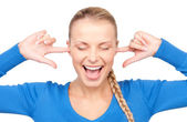 Smiling woman with fingers in ears — Stock Photo
