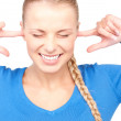 Smiling woman with fingers in ears — Stock Photo #3314847