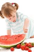 Liten flicka med jordgubb och vattenmelon — Stockfoto