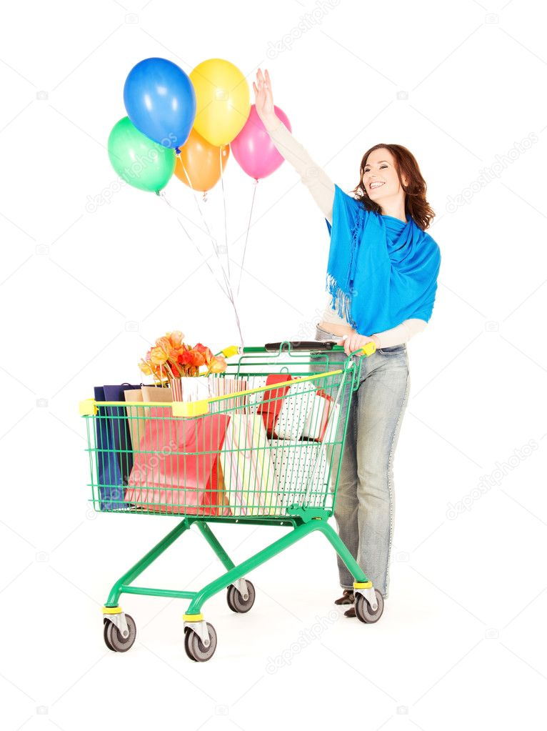Happy woman with shopping cart and balloons over white  Stock Photo #3330493
