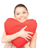 Woman with red heart-shaped pillow over white — Stock Photo
