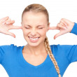 Smiling woman with fingers in ears — Stockfoto