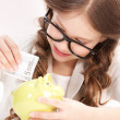 Little girl with piggy bank and money — Stock Photo