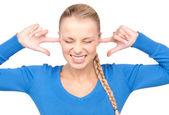 Donna sorridente con le dita nelle orecchie — Foto Stock