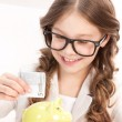Little girl with piggy bank and money — Stock Photo #3467198