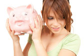 Lovely teenage girl with piggy bank — Stock Photo
