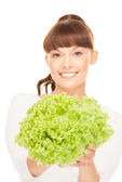 Beautiful housewife with lettuce over white — Stock Photo