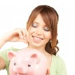 Lovely teenage girl with piggy bank and coin — Stock Photo #3820704