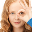 Lovely woman looking through hole from fingers — Stock Photo