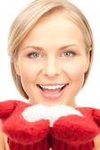 Mooie vrouw in rode wanten met sneeuw — Stockfoto