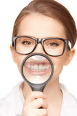 Woman with magnifying glass showing teeth — Stock Photo
