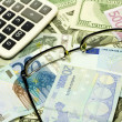 Dollar, euro banknotes, calculator and glasses — Stock Photo