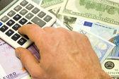 Dollar, euro banknotes, calculator, human hand — Stockfoto