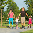 Parents and two daughters skating — Stock Photo