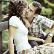Stock Photo: Young couple kissing in the nature - side view.