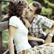 Young couple kissing in the nature - side view. — Stock Photo