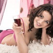Beautiful young brunette holding a glass of red wine — Stock Photo