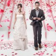 Wedding couple walking in roses - Stok fotoğraf
