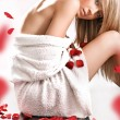 Young blond wearing white towel on rose petals — Stockfoto
