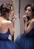 Pretty brunette doing make up looking at the mirror - vintage look — Stock Photo