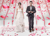 Wedding couple walking in roses — Stock fotografie