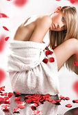 Young blond wearing white towel on rose petals — Stock Photo