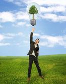 Businessman reaching green energy symbol — Stock Photo
