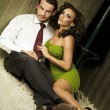 An attractive couple sitting on the floor - Stockfoto