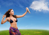 Young beautiful woman sprays clouds on a sunny day — Stock Photo