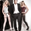 Royalty-Free Stock Photo: Glamour style studio shot of a man and 2 women