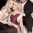 Glamour style studio shot of a man and 2 women - Stock fotografie