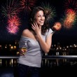 Foto Stock: Beautiful brunette on a fireworks background