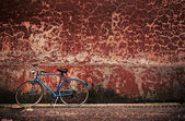 Old retro bicycle over grungy wall — Stock Photo