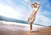 Beautiful young girl walking on the beach — Stock Photo